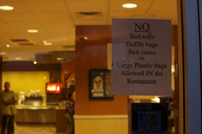 Sign prohibiting entrance to individuals perceived to be homeless at local fast-food restaurant in the downtown area of Phoenix, Arizona.