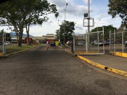 """Entrada principal del Hospital """"Dr. Patricio Peñuela Ruiz"""". Sin rampa de accesibilidad, acera contínua hasta el punto de acceso principal y con el portón principal interrumpiedo el paso peatonal."""