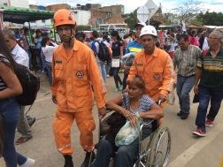 """Personal de Defensa Civil Colombiana ayudando a venezolana comprando productos básicos en """"La Parada"""" Colombia. 17 de Julio de 2016"""